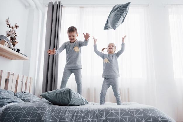 Szczęśliwe dzieci bawiące się w białej sypialni. mały chłopiec i dziewczynka, brat i siostra bawią się na łóżku w piżamie. bielizna nocna i pościel dla niemowląt i małych dzieci. rodzina w domu.