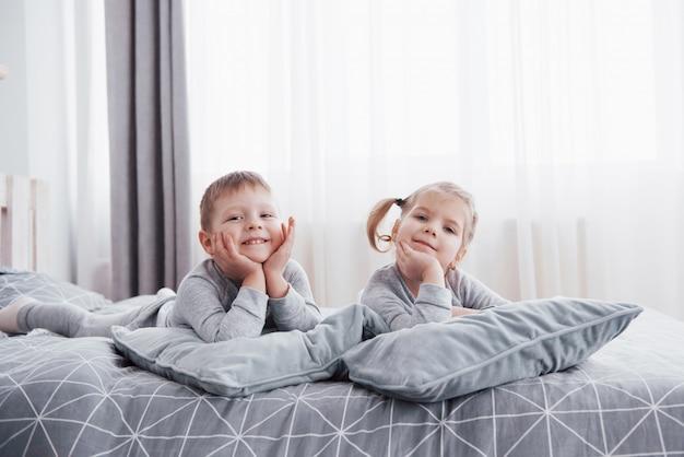 Szczęśliwe dzieci bawiące się w białej sypialni. mały chłopiec i dziewczynka, brat i siostra bawią się w łóżku w piżamie. wnętrze pokoju dziecięcego. bielizna nocna i pościel dla niemowląt i małych dzieci. rodzina w domu