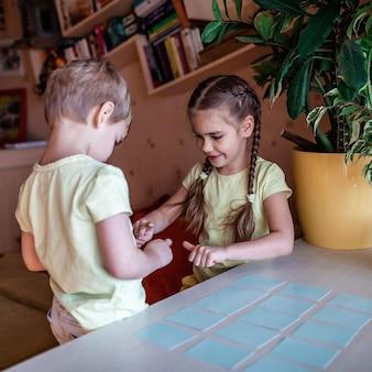 Szczęśliwe dzieci bawiące się w memo z gry planszowej we wnętrzu domowym, wartości rodzinne, pobyt w domu, życie podczas kwarantanny