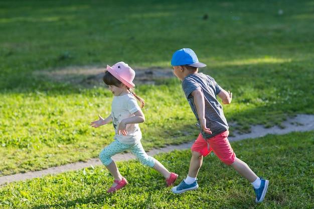 Szczęśliwe dzieci biegają na zewnątrz grając w koncepcję doganiania.