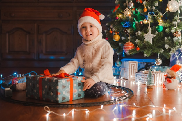 Szczęśliwe dzieci chłopca w santa hat z prezentem mają boże narodzenie lub nowy rok.
