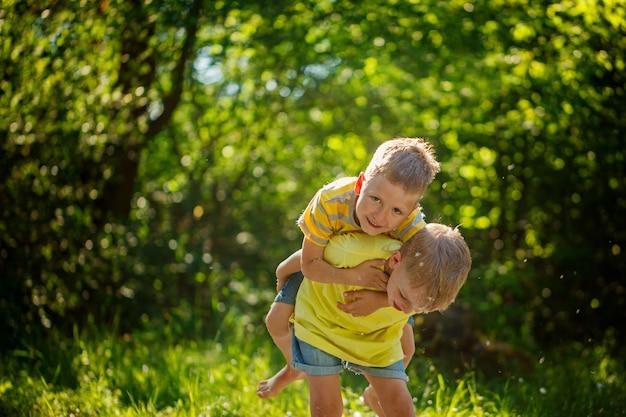 Szczęśliwe dzieci, chłopcy przyjaciele, bawiący się w letnim parku, dzieci ha