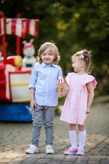 Szczęśliwe dzieci, chłopiec i dziewczynka jedzą lody w wesołym miasteczku