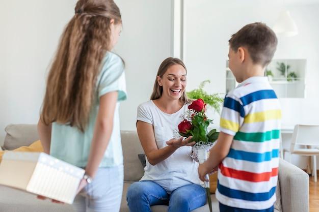 Szczęśliwe dzieci dające w prezencie kwiaty matce. szczęśliwego dnia matki! dzieci chłopiec i dziewczynka gratulują uśmiechniętej mamie, wręczają jej bukiet kwiatów z róż i pudełko prezentowe podczas świątecznych uroczystości