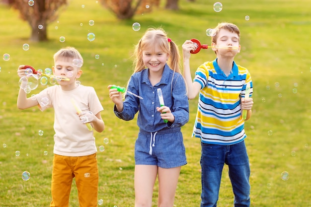 Szczęśliwe dzieci dmuchają baniek mydlanych w lecie parku.