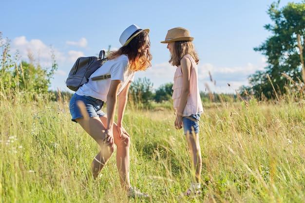 Szczęśliwe dzieci dwie dziewczyny siostry nastolatka i młodsze śmieją się i bawią na łące, błękitne niebo, letnia natura