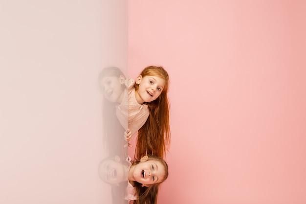 Szczęśliwe dzieci, dziewczyny na białym tle na koralowy róż