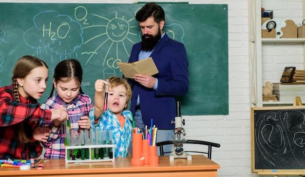 Szczęśliwe dzieci i nauczyciel. robienie eksperymentów z cieczami w laboratorium chemicznym. laboratorium chemiczne. powrót do szkoły. dzieci w fartuchu nauka chemii w szkolnym laboratorium. potrzebują fachowej porady.