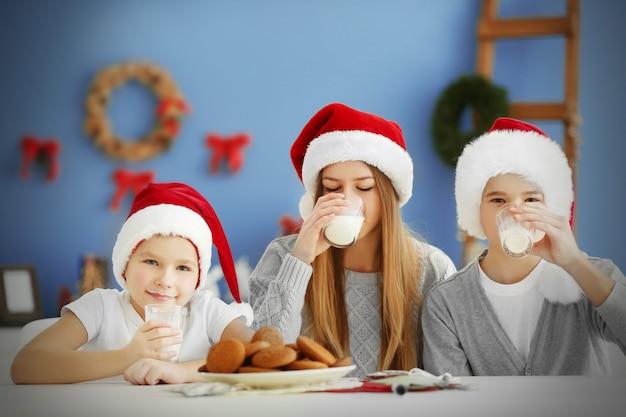 Szczęśliwe dzieci jedzą posiłek w udekorowanej świątecznej sali