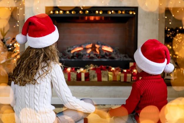 Szczęśliwe dzieci kominku na boże narodzenie. dzieci bawią się w domu.