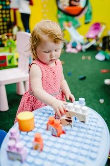 Szczęśliwe dzieci, mała dziewczynka bawi się zabawkami edukacyjnymi w dziecięcym pokoju zabaw w swoje urodziny. przedszkole. przedszkole. impreza w parku rozrywki dla dzieci i centrum zabaw w pomieszczeniach.