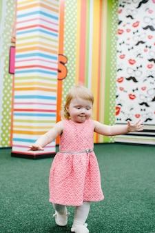 Szczęśliwe dzieci, mała dziewczynka biega i bawi się w pokoju zabaw dla dzieci w swoje urodziny. przedszkole. impreza w parku rozrywki dla dzieci i centrum zabaw w pomieszczeniu.