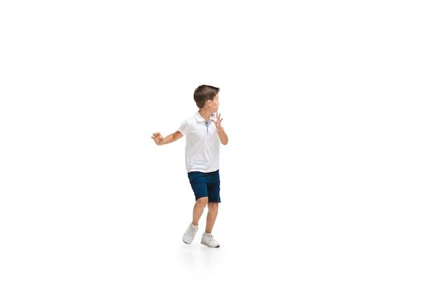 Szczęśliwe dzieci, mały i emocjonalny chłopiec kaukaski skaczący i biegający na białym tle