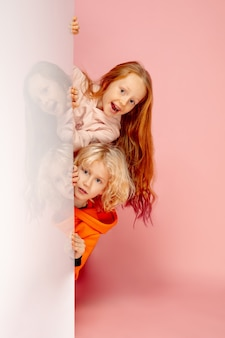Szczęśliwe dzieci na białym tle na tle koralowego różowego studia. wygląda na szczęśliwego, wesołego, szczerego. copyspace. dzieciństwo, edukacja, koncepcja emocji