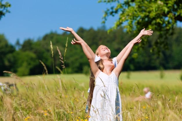 Szczęśliwe dzieci na łące, podnosząc ręce do góry na niebie