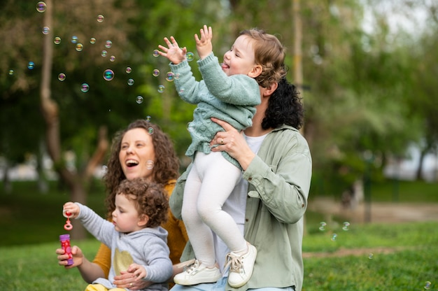 Szczęśliwe dzieci na świeżym powietrzu w parku z matkami lgbt