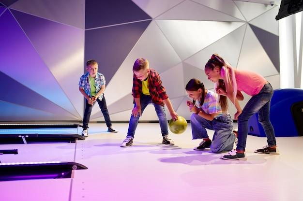 Szczęśliwe dzieci na torze w kręgielni. dzieci przygotowują się do uderzenia. chłopcy i dziewczęta bawią się razem w centrum rozrywki