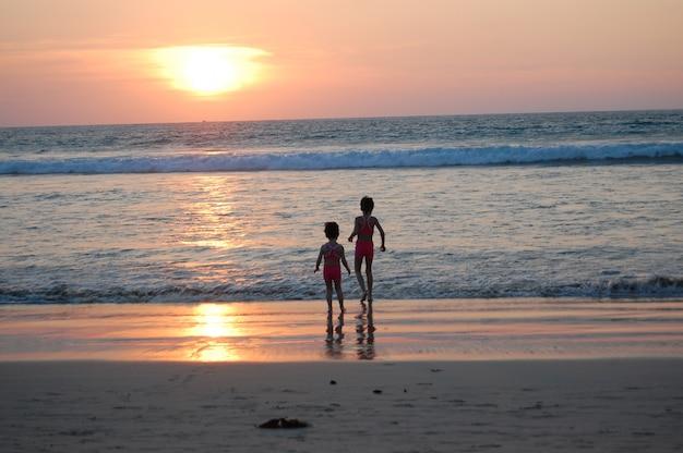 Szczęśliwe dzieci na wakacjach na plaży. małe dziewczynki biegnące w pobliżu morza