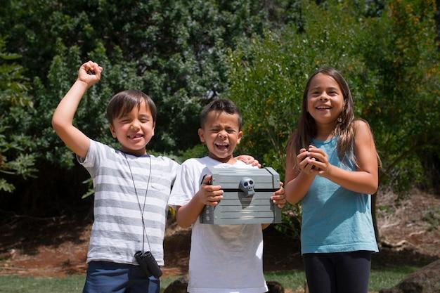 Szczęśliwe dzieci odnajdujące skarb podczas poszukiwania skarbów