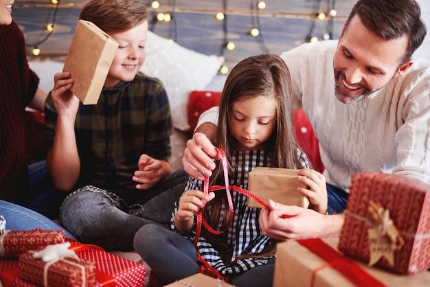 Szczęśliwe dzieci otwierające świąteczny prezent z rodzicami
