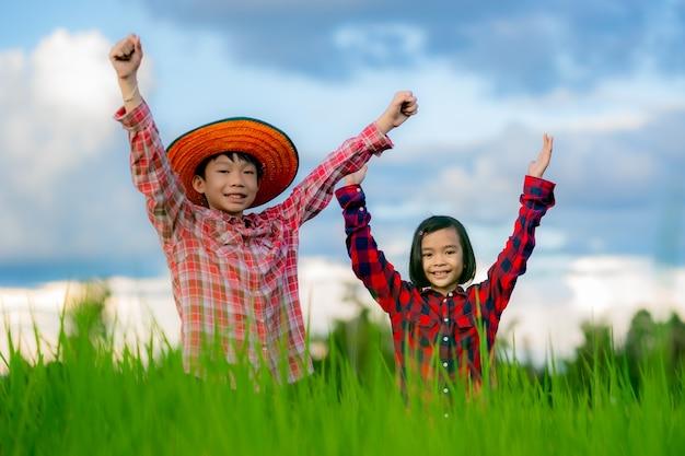 Szczęśliwe dzieci podnoszą rękę i uśmiechają się w ryżowym polu ekologicznych pól uprawnych na tle błękitnego nieba