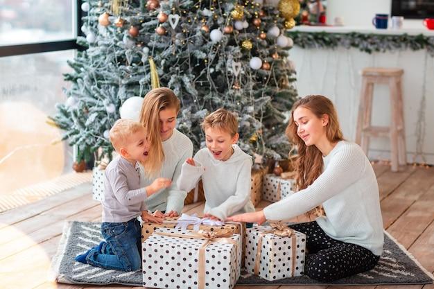 Szczęśliwe dzieci przy choince z prezentami