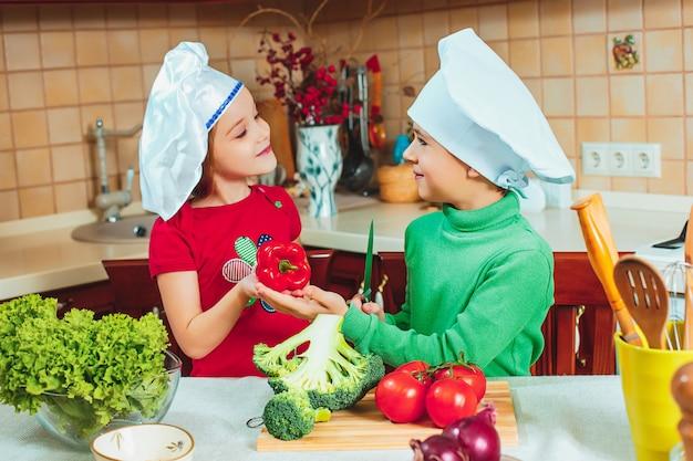 Szczęśliwe dzieci przygotowują sałatki ze świeżych warzyw w kuchni