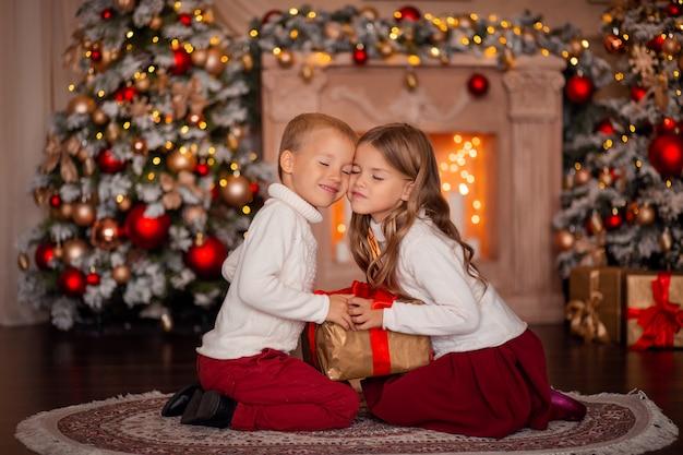 Szczęśliwe dzieci przytulanie w pobliżu drzewa nowego roku w oczekiwaniu na wakacje nowego roku