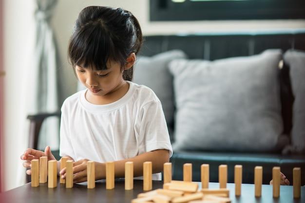 Szczęśliwe dzieci radośnie bawią się w domu drewnianymi klockami