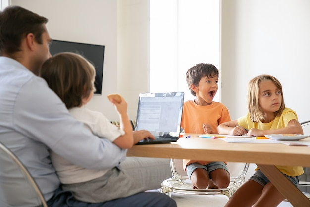 Szczęśliwe dzieci rysują gryzmoły, gdy tata pracuje na laptopie i trzyma syna na kolanach. wychodzące dzieci malujące na papierze. kaukaski rodzina siedzi przy stole. koncepcja dzieciństwa, kreatywności i weekendu