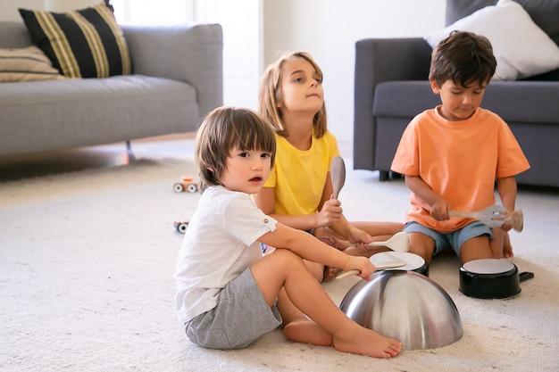 Szczęśliwe dzieci siedzą na dywanie i bawią się naczyniami. śliczni kaukascy mali chłopcy i blondynka bawią się razem w salonie i pukają do patelni. koncepcja aktywności dzieci i domu