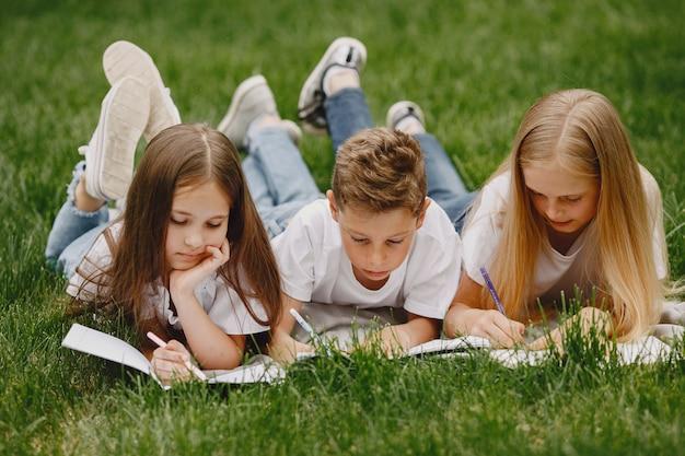 Szczęśliwe dzieci siedzą razem blisko i uśmiech