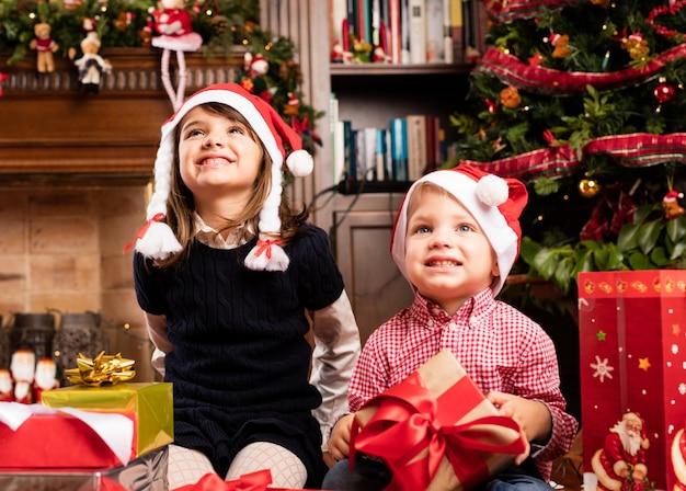 Szczęśliwe dzieci siedzi w salonie na boże narodzenie