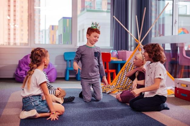 Szczęśliwe dzieci. szczęśliwy dzieciak brunetka siedzi w pozycji pół i patrząc na swojego brata