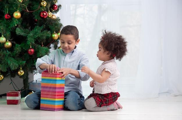 Szczęśliwe dzieci trzyma prezenty i siedzi na podłodze