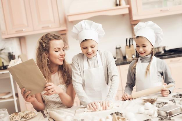 Szczęśliwe dzieci ugniatają mamę ciasta w uśmiechu.