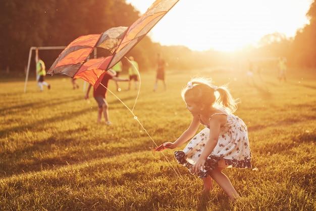 Szczęśliwe dzieci uruchamiają latawiec w polu o zachodzie słońca. mały chłopiec i dziewczynka na wakacjach