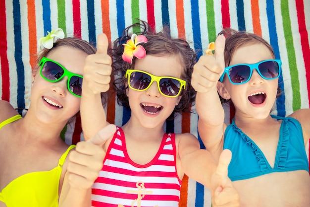 Szczęśliwe dzieci w kolorowych okularach przeciwsłonecznych kładą się i robią ok znak na kolorowym ręczniku plażowym w paski