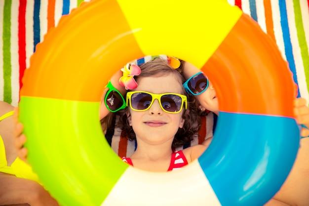 Szczęśliwe dzieci w kolorowych okularach przeciwsłonecznych z okrągłym dmuchawcem na kolorowym ręczniku plażowym w paski