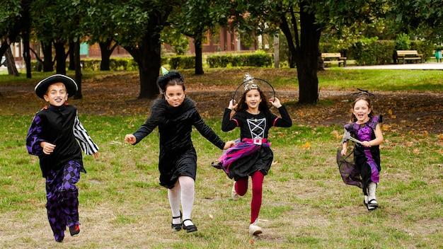 Szczęśliwe dzieci w kostiumach na halloween na trawniku