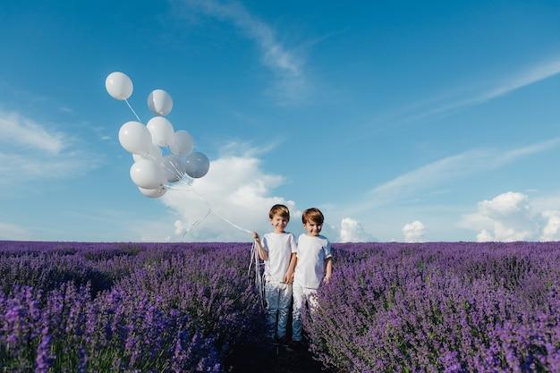 Szczęśliwe dzieci w lawendowym polu z białymi balonami w słoneczny dzień na zewnątrz