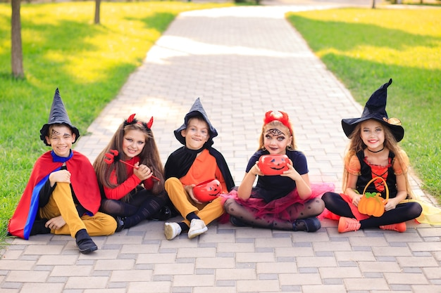 Szczęśliwe dzieci w parku w kostiumach na halloween świętują święto