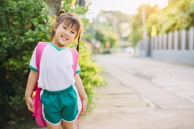 Szczęśliwe dzieci w stroju studenckim i torbie gotowe do nauki w szkole