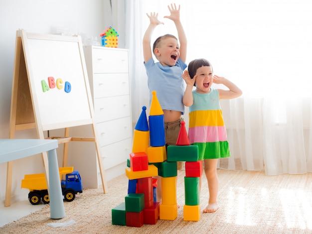 Szczęśliwe dzieci w wieku przedszkolnym bawić się klockami zabawki.