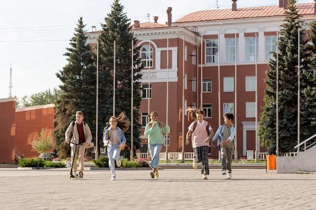 Szczęśliwe dzieci w wieku szkolnym biegnące po dużym placu wracając ze szkoły