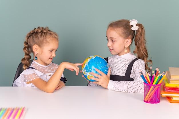 Szczęśliwe dzieci w wieku szkolnym chłopiec i dziewczynka razem uczą się w szkole