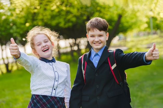 Szczęśliwe dzieci w wieku szkolnym, dając kciuki do góry gest zatwierdzenia i sukcesu.