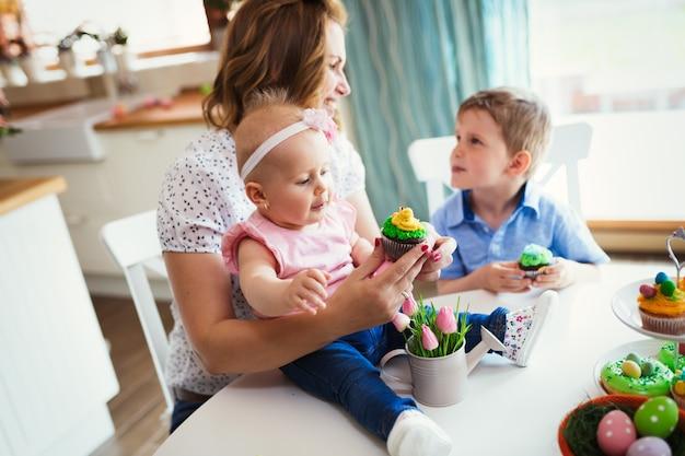 Szczęśliwe dzieci z matką jedzą babeczki w scenie wielkanocnej