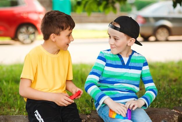 Szczęśliwe dzieci zabawy na świeżym powietrzu. śliczni chłopcy bawią się modną zabawką pop it. przyjaciele na spacerze z silikonowymi zabawkami bąbelkowymi. nowoczesna zabawka antystresowa dla dzieci. dzieciństwo, gry i rozrywka dla dzieci.