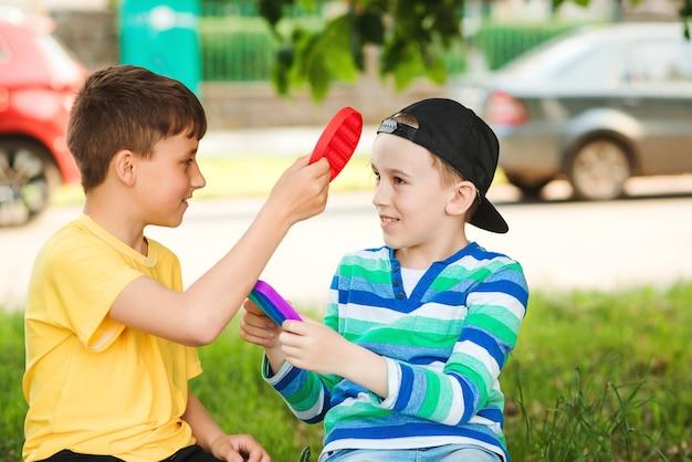 Szczęśliwe dzieci zabawy na świeżym powietrzu. śliczni chłopcy bawią się modną zabawką pop it. przyjaciele na spacerze z silikonowymi zabawkami bąbelkowymi. nowoczesna zabawka antystresowa dla dzieci